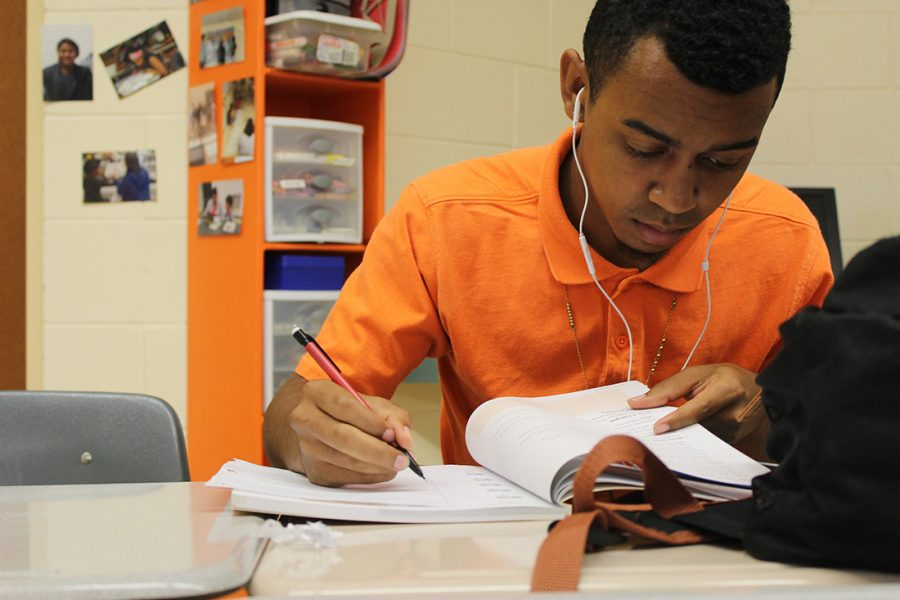 While planning his research paper, sophomore Jordan Thomas consults his textbook. Photo by Grace Gillen