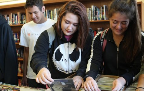 Looking for the perfect find, senior Brooke Scotton pulls out comic books from their display. Photo by Grace Gillen