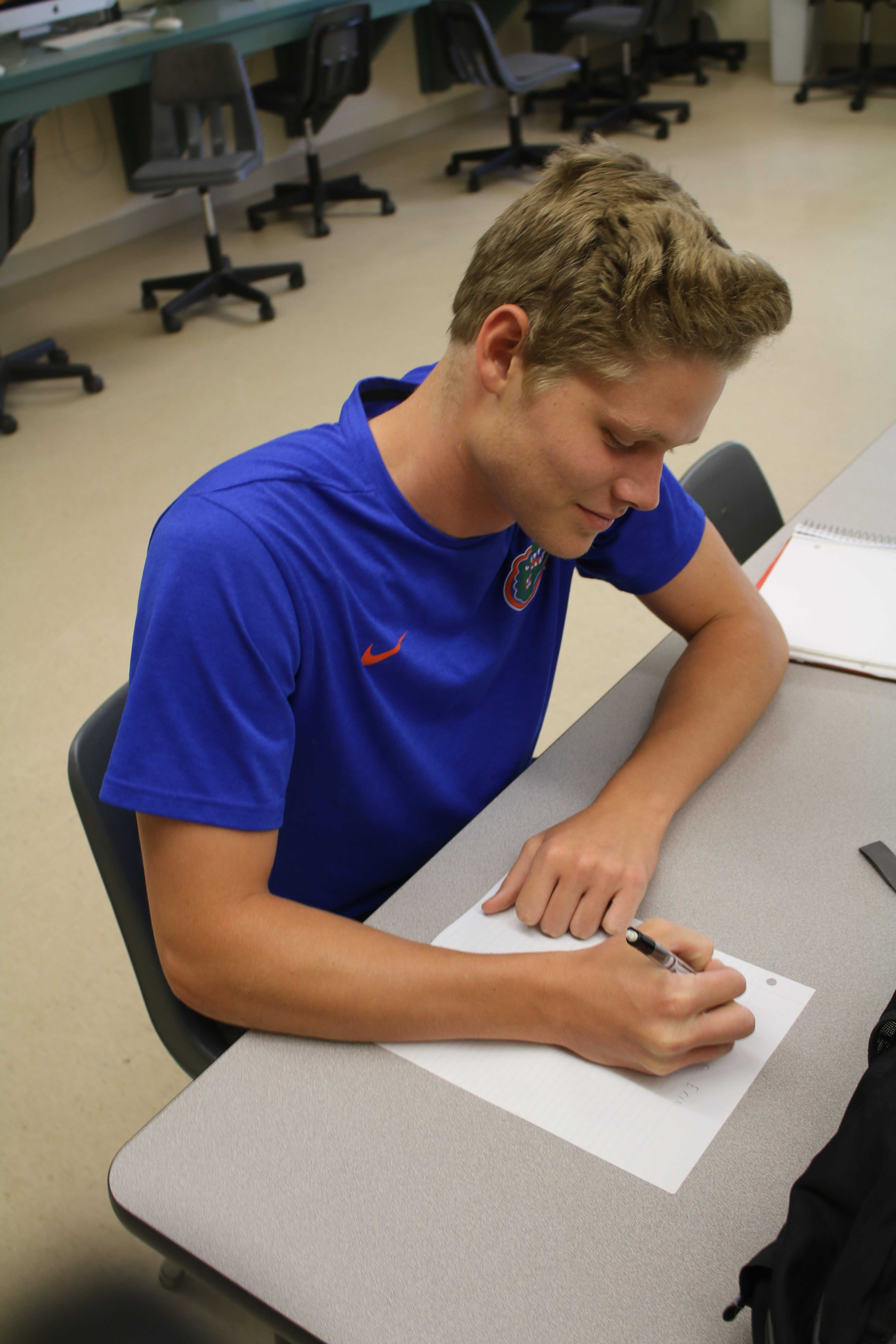 """With a smile on his face, sophomore Eric Hartless writes his response letter to his pen pal, Khloe. She asked him if he liked Frozen, and what his favorite sport was. """"It's a cool idea to care about little kids as a team, and talk about our lives with them,"""" Hartless said. """"They look up to us, so I'm sure when we write them, it makes them feel important."""""""