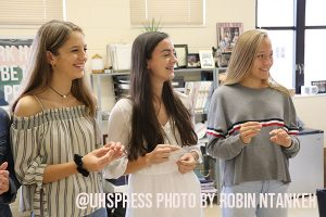 """(From left to right) Yearbook staffers and sophomores, Briahna Martin, Chloe Evers, and Natasha Sweet, laugh at joke being said by one of their fellow staffer members and proceed to slip on their rings when they recite the group vow. """"So for yearbook, all you have to do is to work really hard,"""" Natasha said. """"You have to spend time on it and with the wedding, that was kind of just a validation that you are going to do it and I thought it was really cool."""""""