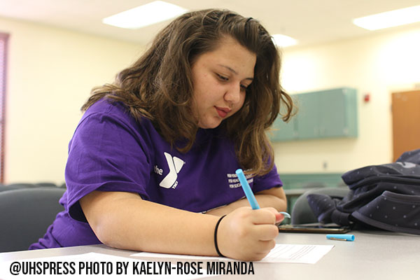 Junior Elana Feliciano fills out a scholarship paper.