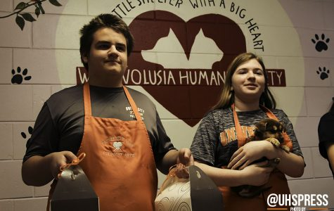 "(From left to right) While preparing to pose for a group photo, freshman Nicholas Rachmaninow and sophomore Beth Anne Wright stand in front of the entrance of the West Volusia Humane Society with wide smiles and treats in hand. ""I would love to do this type of event again because it gives me a chance to do what I love to do the most: cook,"" Rachmaninow said. ""It's a passion that I've always had and to able be to share that with people, and animals, is truly amazing."""