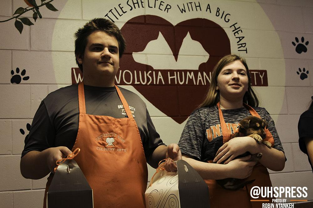 """(From left to right) While preparing to pose for a group photo, freshman Nicholas Rachmaninow and sophomore Beth Anne Wright stand in front of the entrance of the West Volusia Humane Society with wide smiles and treats in hand. """"I would love to do this type of event again because it gives me a chance to do what I love to do the most: cook,"""" Rachmaninow said. """"It's a passion that I've always had and to able be to share that with people, and animals, is truly amazing."""""""