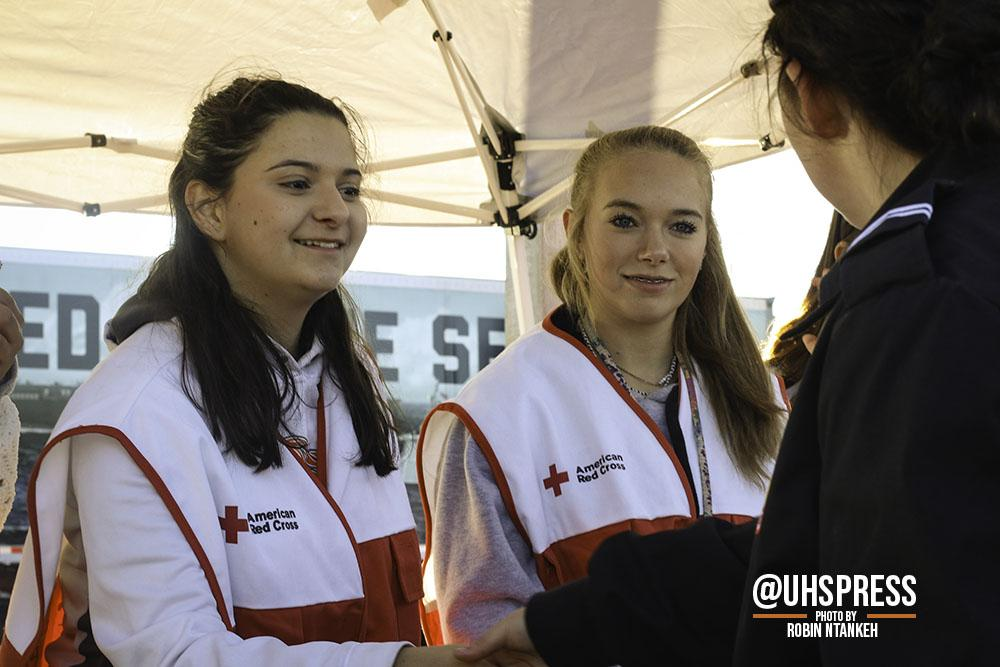 "(From left to right) With friendly smiles and tons of energy, sophomores and Red Cross Club members Hailey Banks and Katie Vandehey helped students practice hands-only CPR and what to do incase of a medical emergency. ""The Red Cross Club prepared me for the military expo because we became presenters to teach hands-only CPR to the other students who dropped by our booth…"" Hailey said. ""I would definitely do it again because it was a fantastic experience that taught me a lot."""