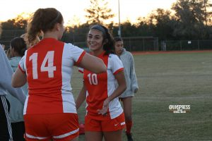 With bright smiles, senior Natalia Diaz goes in for a celebration hug with sophomore Brea Kamm after winning the district semi finals.