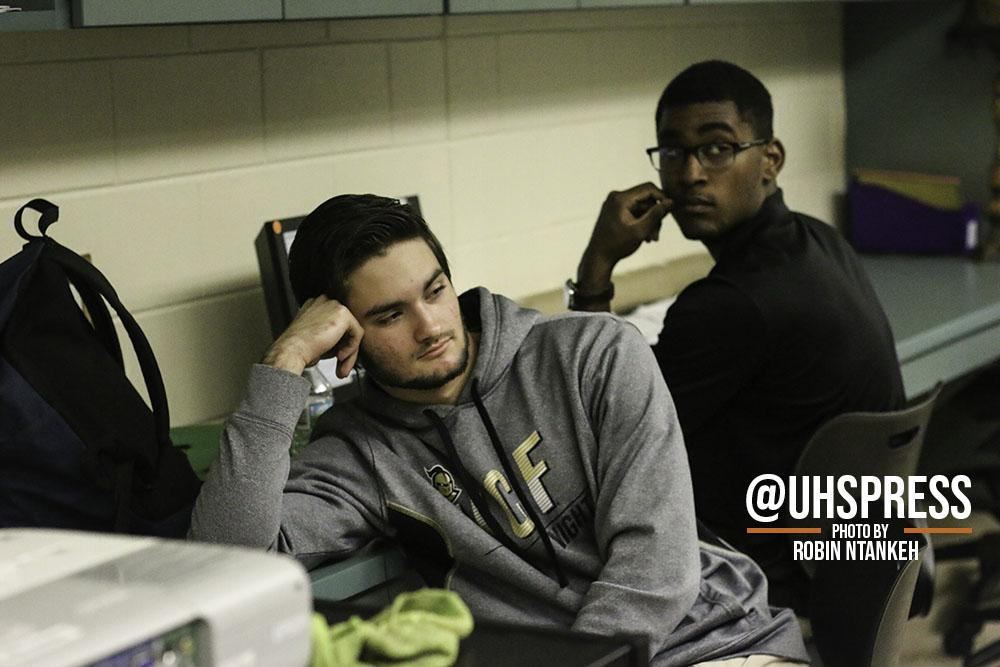 """(From left to right) Seniors Richard Gailey and Frank Font observe the ongoing lecture from the students while busying themselves with their own homework or listening to music on their phones. """"As their peer counselor, I help them with anything they need such as homework, or calculating their grades,"""" Font said. """"I say it's enjoyable for the most part and my favorite part about the whole class is being able to do nothing and not get in trouble for it. And also working on my own work from other classes.... I hope to use this experience on my resume for college and study electrical engineering as my career."""""""