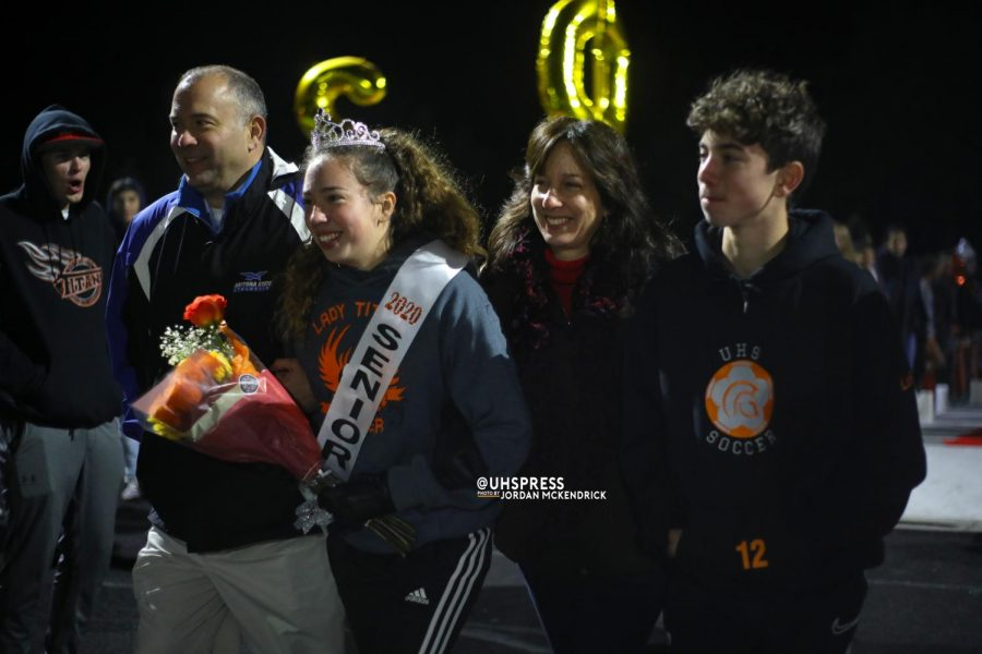 "With a flower bouquet in hand, senior Alexa LoBasso walks down the field, escorted by her family on senior night. LoBasso started on the team as a freshman and knew this night would not be easy. ""I have seen everyone else do it for the past three years and now it was my turn,"" LoBasso said. ""It was an emotional moment."""