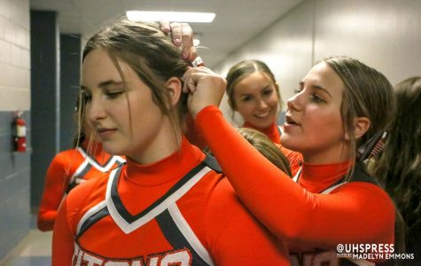 Waiting to go on the competition mat, sophomore Marissa Hudick fixes her teammates bow. Junior Kori Kestory had help from a cheer sister.